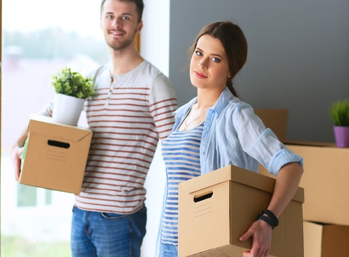 Happy young couple packing boxes and moving into a new home